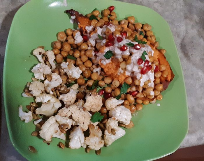half a baked sweet potato covered in roasted chickpeas, tahini dressing, and pomegranate seeds. Roasted cauliflower with browned butter and pumpkin seeds