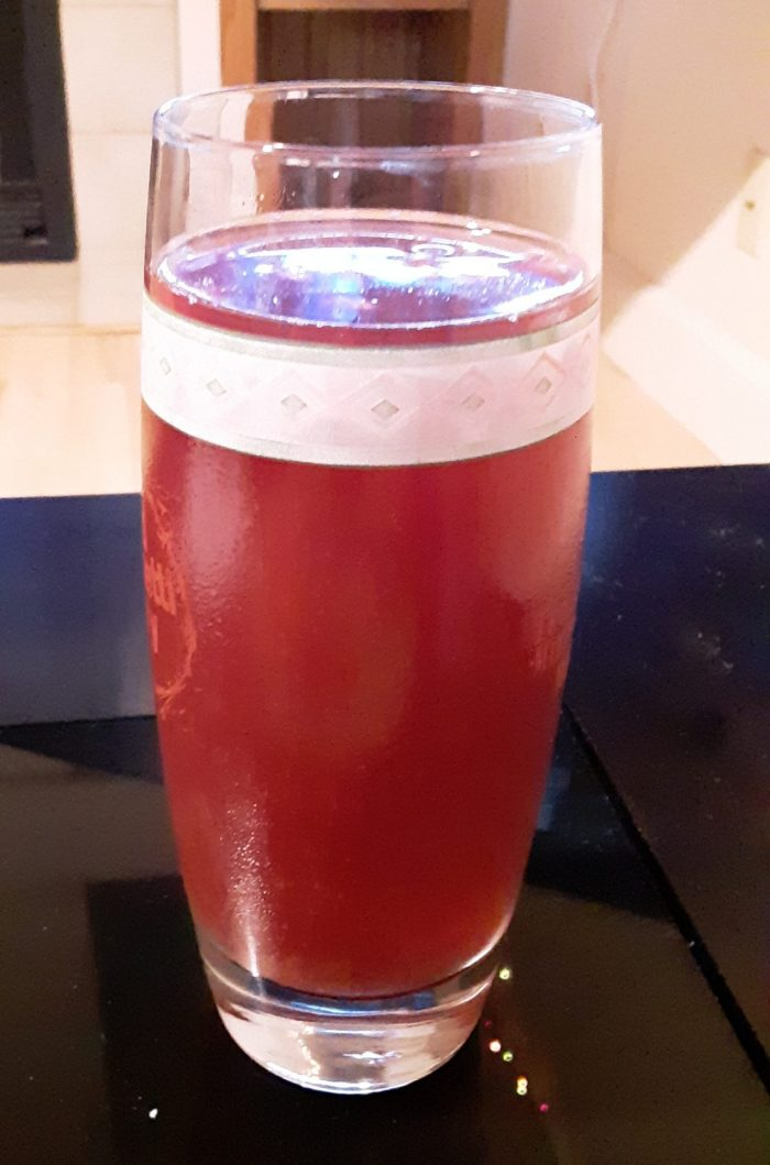 a glass containing a red mixed drink