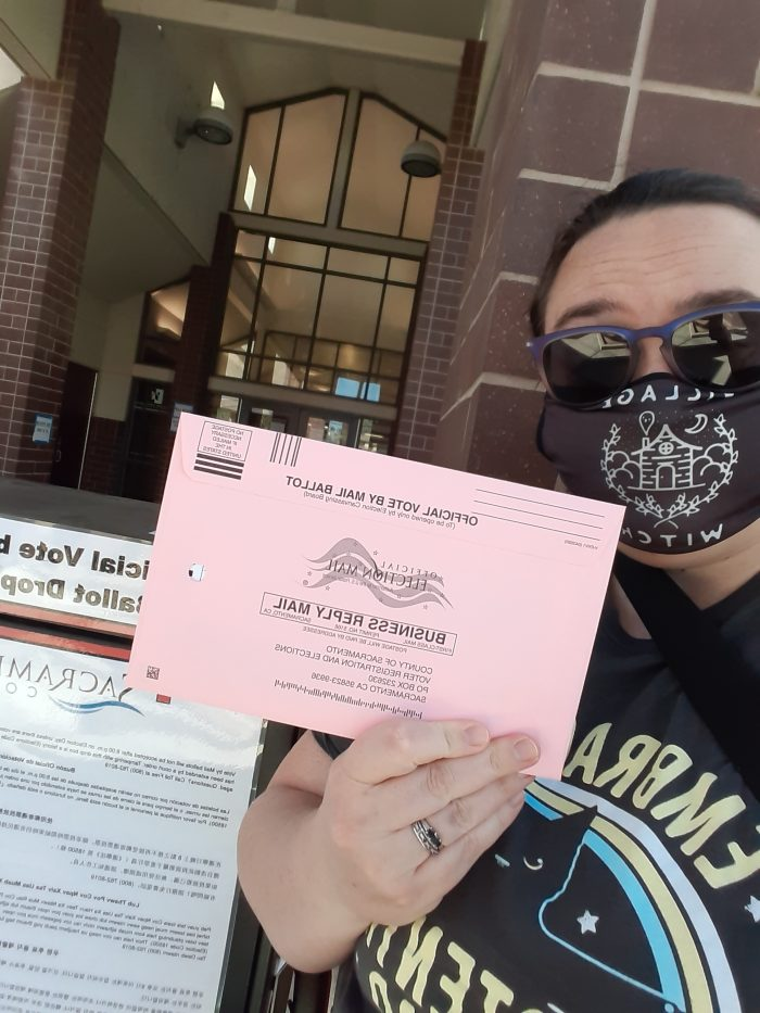 a selfie of me holding up my ballot in front of the ballot drop box at the library