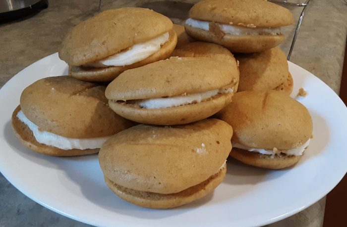 a pile of pumpkin sandwich cookies piled on a plate