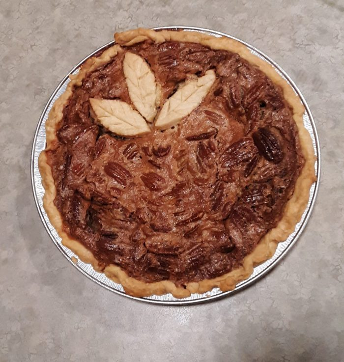 "a pecan pie with three pie dough ""leaves"" on top for decoration"