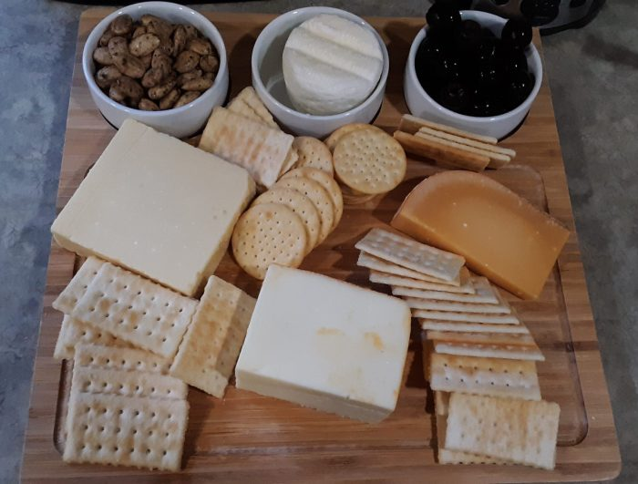 a wooden board covered with several types of cheese and crackers plus almonds and olives