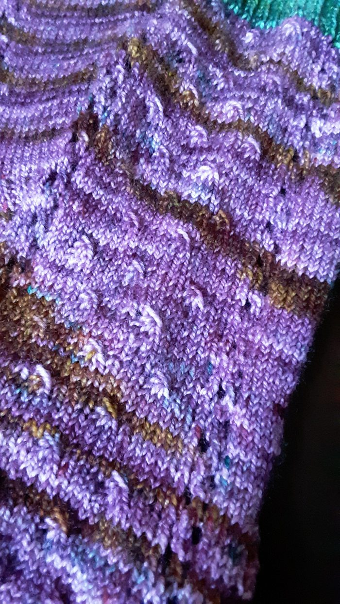 a close up of the design details in the luminary sock including eyelets and other texture