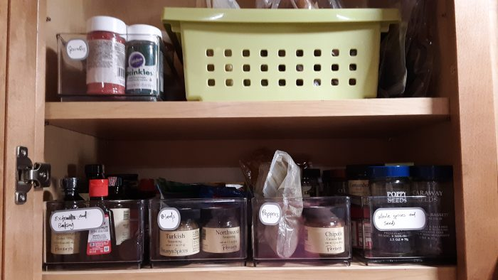two pantry shelves, now with thin, clear plastic bins holding a variety of spice jars and related ingredients