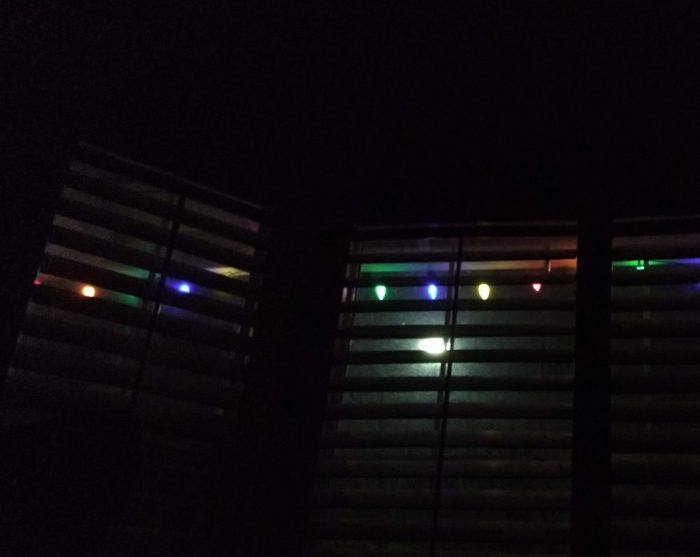 a view of the christmas lights through shutters titlted partially open