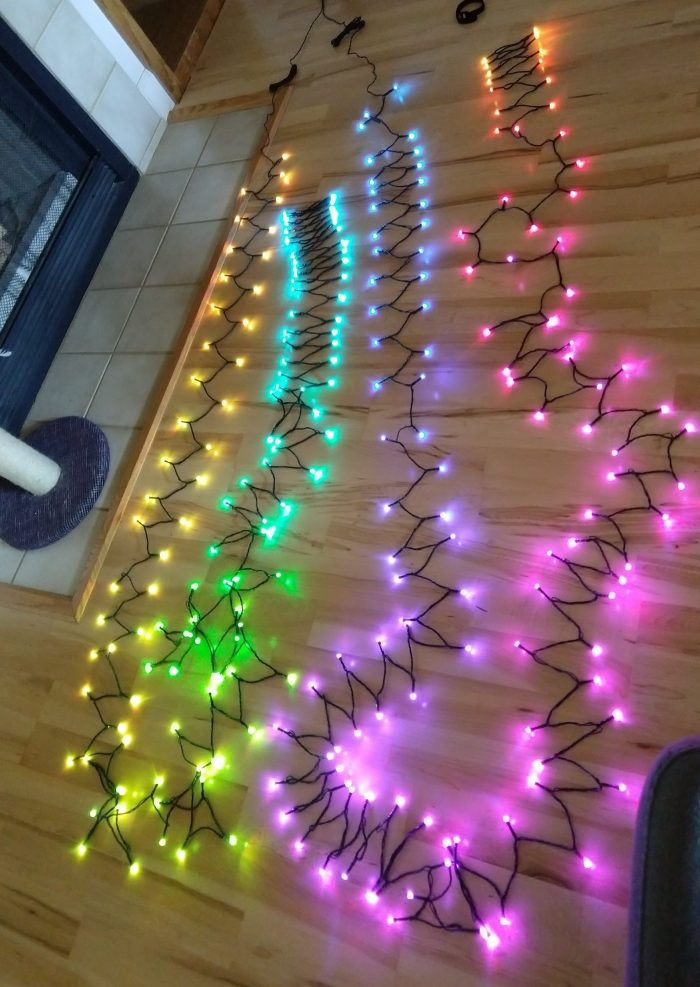 a long strand of lights wound around on the floor, light in rainbow colors