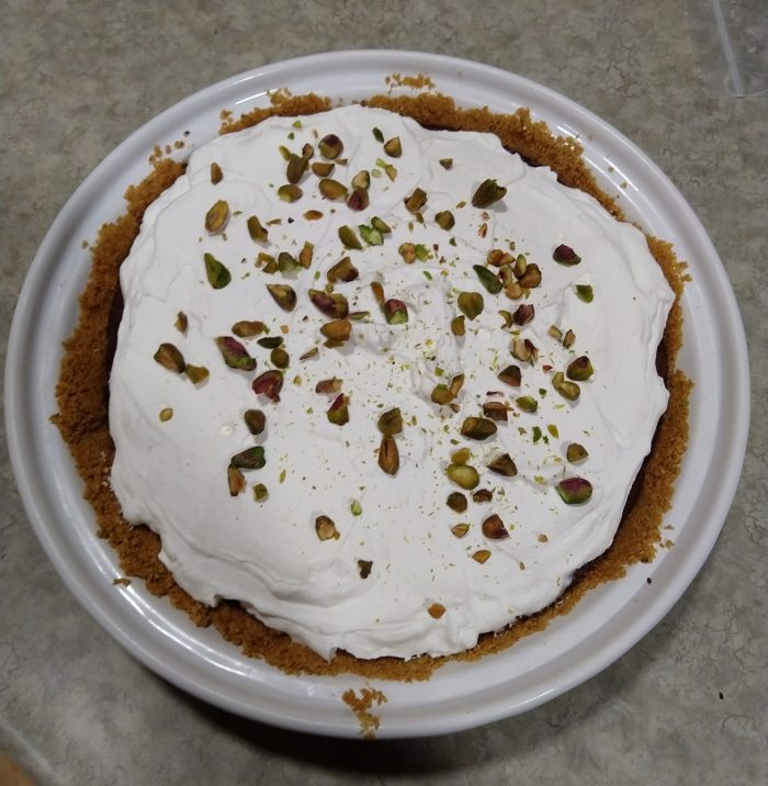 a cream pie in a white ceramic dish. The top is a layer of whipped cream with chopped pistachios