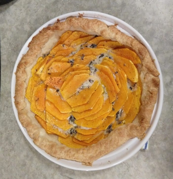 butter nut squash and blue cheese tart in a round dish