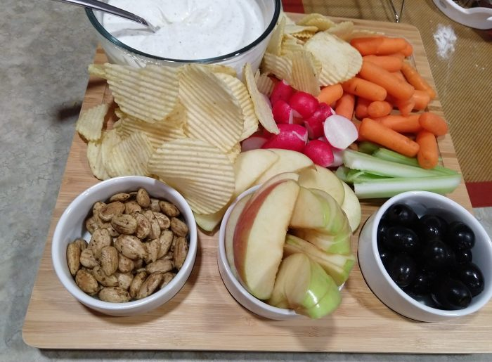 wooden snack board with olives, apples, almonds, chips, radishes, celery, carrots, and ranch dip