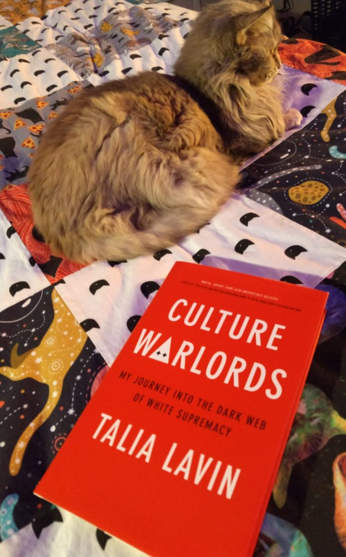 book Culture Warlords, which has a red cover and white text, next to Viola the cat