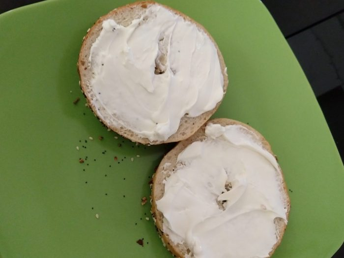 everything bagel cut in half with cream cheese spread on top