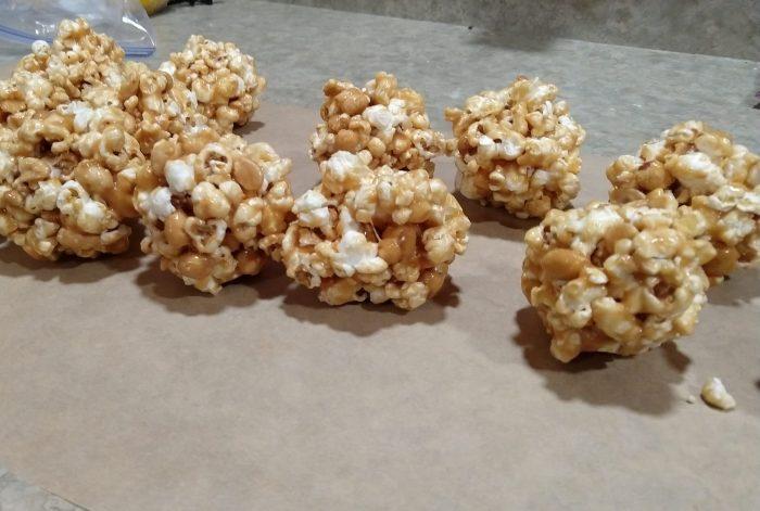about 10 peanut butter popcorn balls on a piece of parchment paper