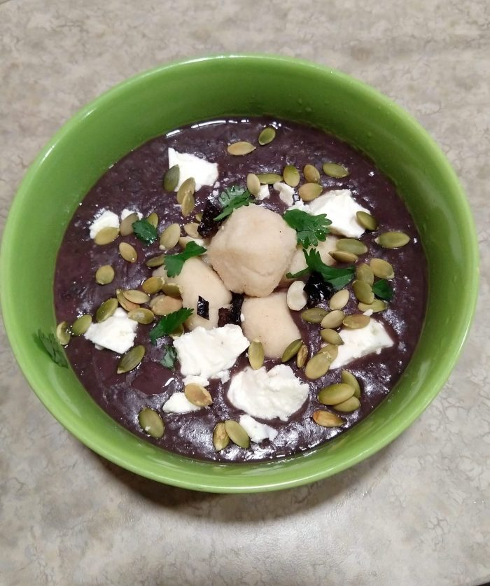 a green bowl filled with black bean soup, which is topped with masa dumplings, pumpkin seeds, feta, cilantro, and dried ancho chili