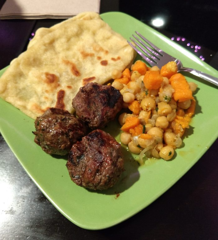 a plate with moroccan flat bread, meatballs, and a chickpea nad sweet potato dish