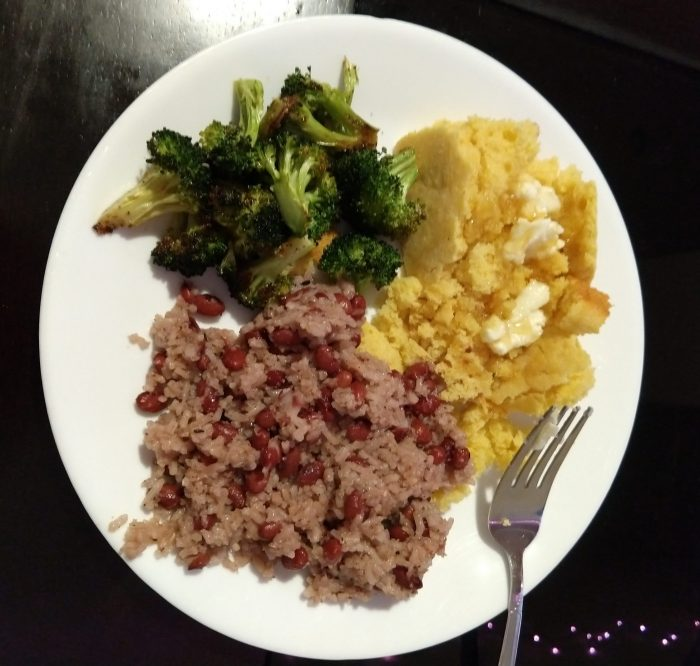a plate with a serving of red beans and rice, cornbread, and roasted broccoli