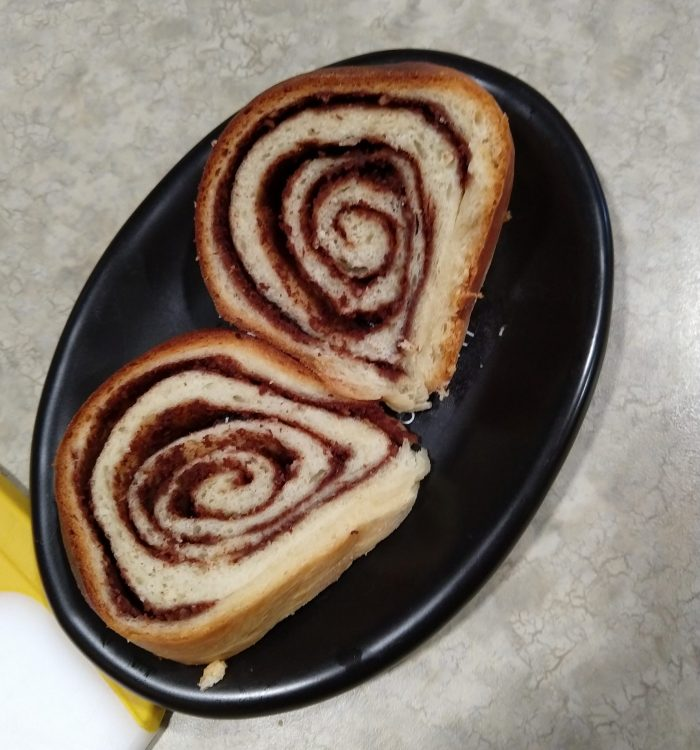 two slices of babka on a small plate, revealing the swirl pattern inside and chocolate filling