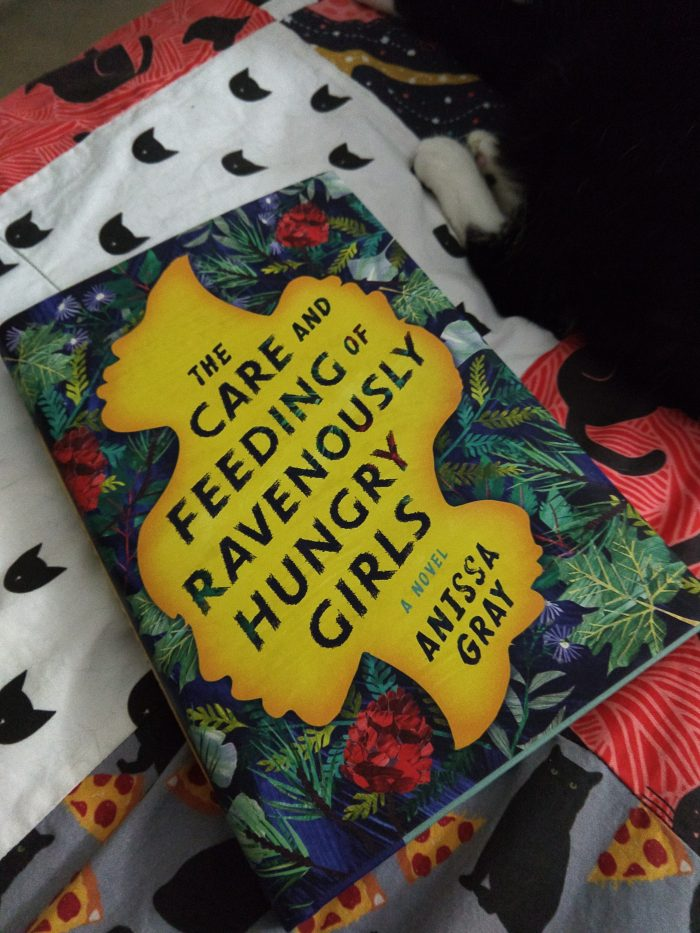 hardcover book The Care and Feeding of Ravenously Hungry Girls. Huey the cats feet visible next to the book
