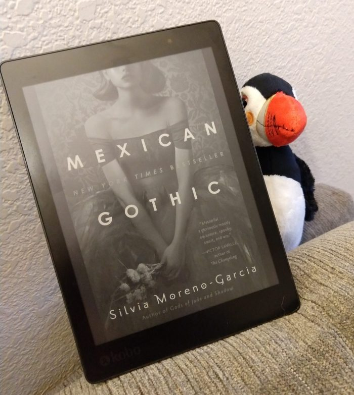 book cover of Mexican Gothic, shown on kobo ereader. Puffin stuffed animal peeking out behind the book