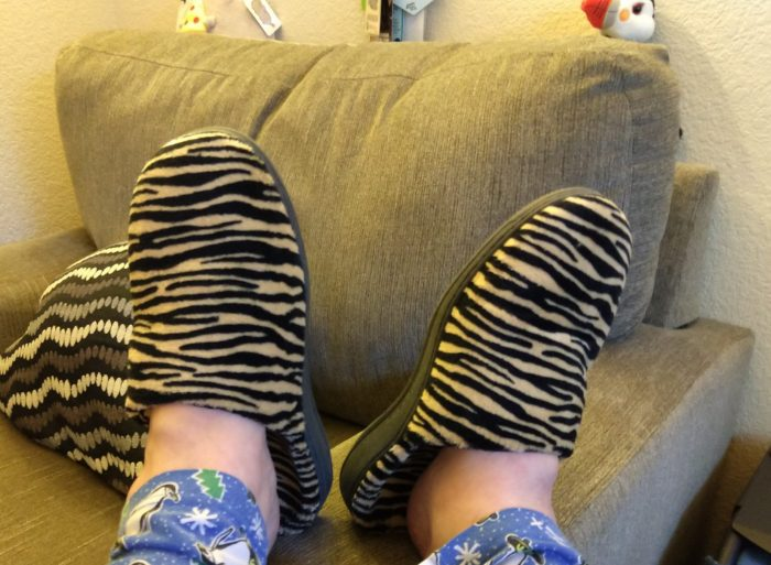 my slipper-clad feet propped up on the side of a chair, showing off my new tiger-print slippers