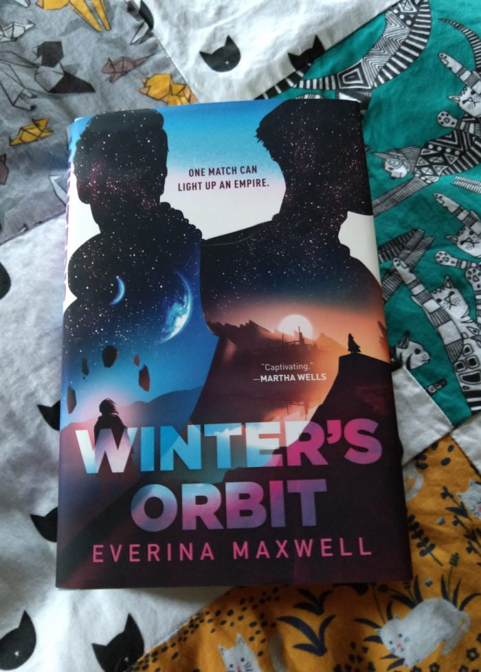 hardback book: Winter's Orbit on top of a colorful quilt made of different cat patterns