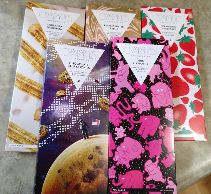 five bars of Compartes chocolate. The packages are colorful and reflect their contents