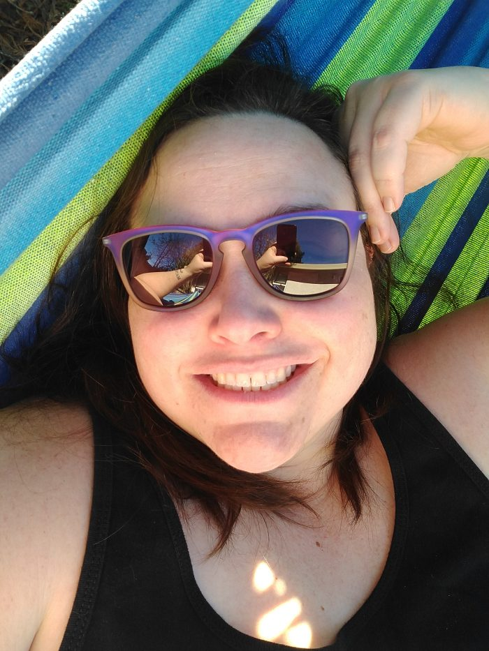 head and shoulders of me in a blue and green hammock. I am wearing purple rimmed sunglasses and smiling at the camera