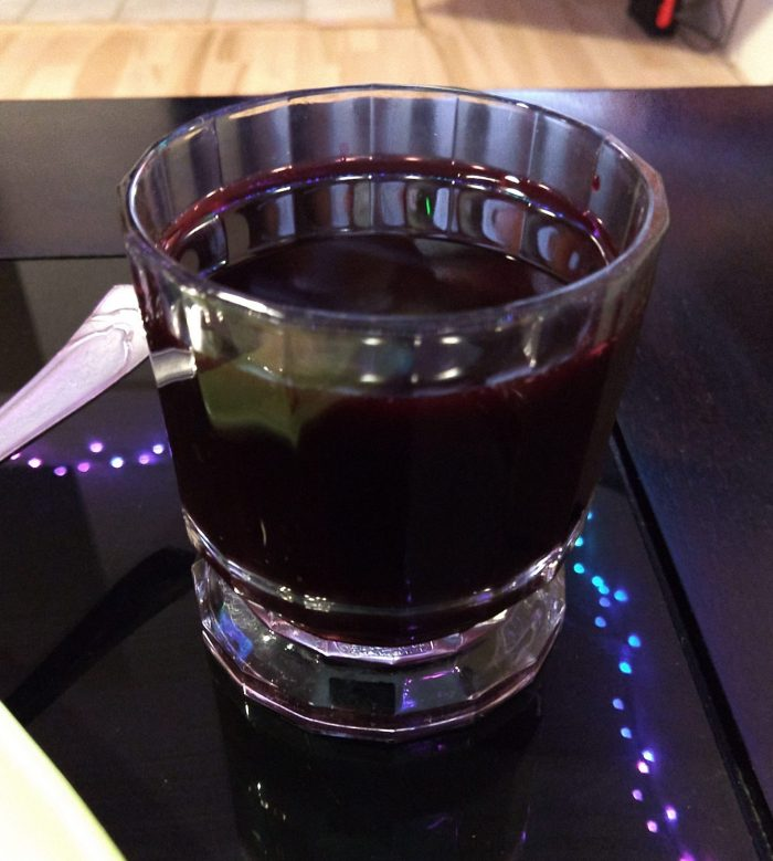 a small glass of chicha morada, a dark-purple colored beverage made out of corn