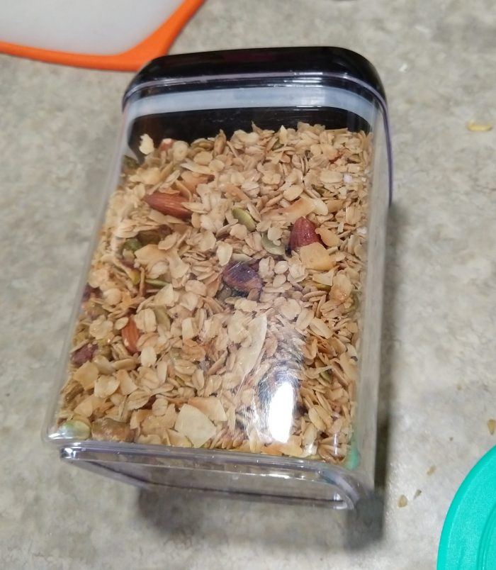 a batch of granola—oats, almonds, pistachios, coconut, and pumpkin seeds–in a rectangular container