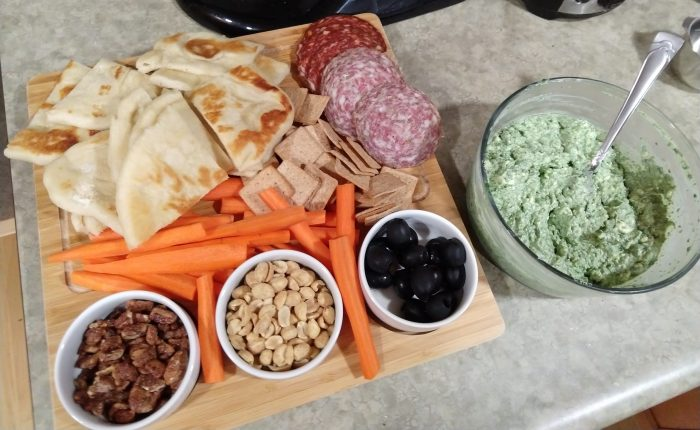 a wooden board covered in pita bread, crackers, carrot sticks, salami, nuts and olives. A bowl of spinach dip is next to the board.