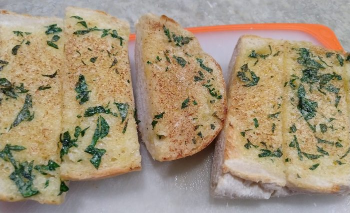several pieces of garlic bread on a cutting board. The bread is perfectly browned and flecked with pieces of parsley