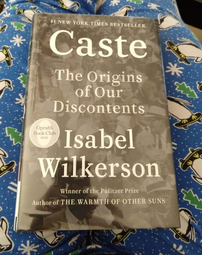 book cover of Caste: the origins of our discontents. The cober shows a crowd of people, perhaps from the 1960s, in black and white