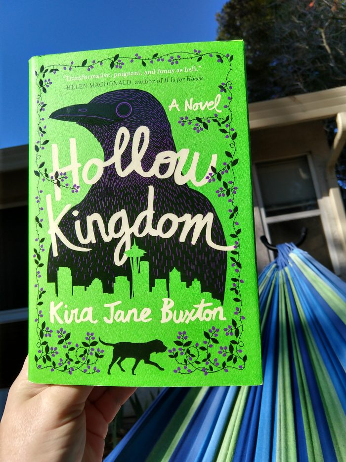hardcover book: Hollow Kingdom. Picture is taken outside with a hammock and blue sky in the background. Book cover is bright green and features a stylized drawing of a crow