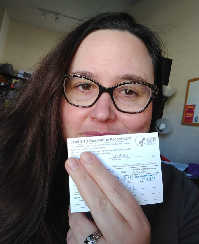 me, holding my covid-19 vaccination card in front of my mouth to show I got my first vaccine