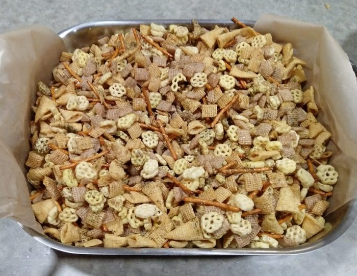 a roasting pan full of furikake chex mix, which includes, chex, bugles, honeycomb, and pretzels flavored with kelp and sesame seed