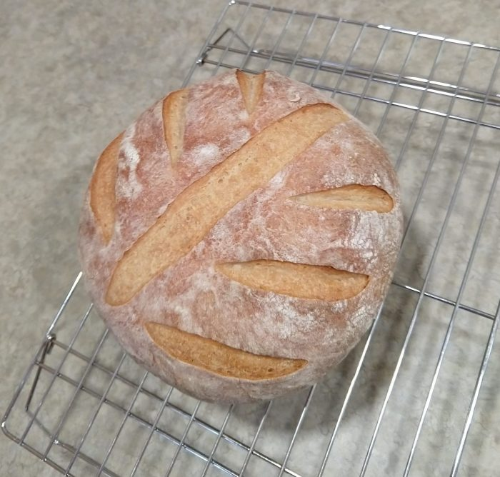 a round of bread scored with a leaf pattern