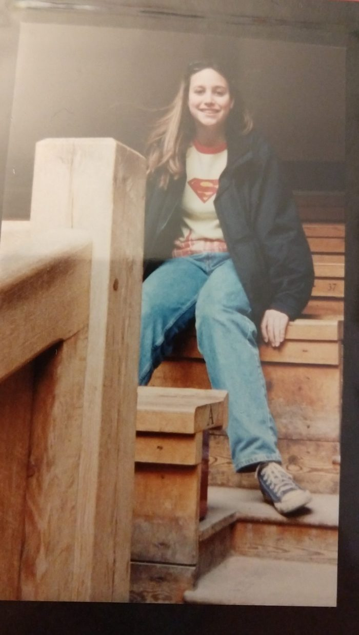 me at age 14, wearing jeans and a jacket, sunglasses on top of my head, smiling at the camera from the stands at the Globe theater in London