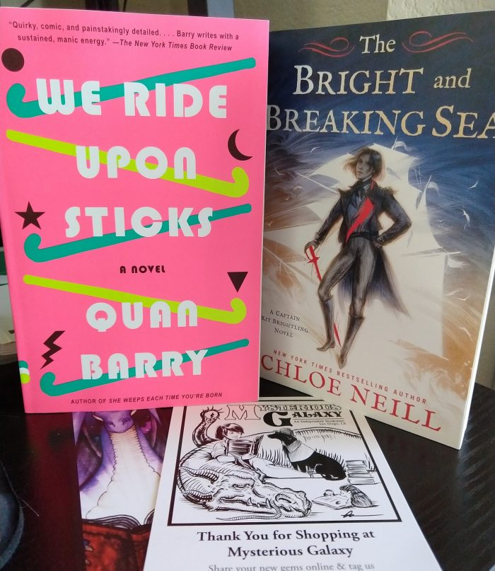 two books: We Ride Upon Sticks and The Bright and Breaking Sea. shown next to a flyer from the bookstore, Mysterious Galaxy