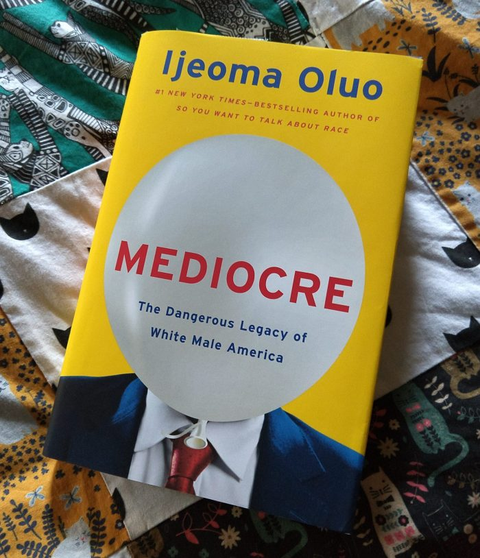 """hardback book """"Mediocre: The dangerous legacy of white male america."""" Book is lying on a quilt made of cat-themed designs"""