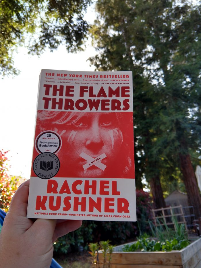 paperback book: The Flamethrowers. Photo taken outside with a garden box and pine trees in the background