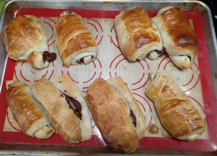 a sheet pan with 8 freshly baked chocolate croissants. Some are in the traditional rectangle shape but others have opened up and lost the shape during baking