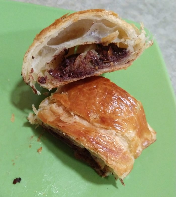 cross section of chocolate croissant revealing a flaky interior and a big layer of chocolate