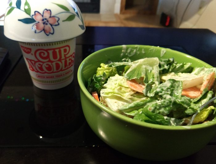 a bowl of salad and a cup noodles with a tiny bowl inverted on top (to keep the heat in while it cooks)