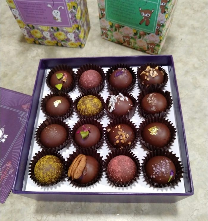 an open box of chocolate showing 16 small truffles garnished with a variety of toppings