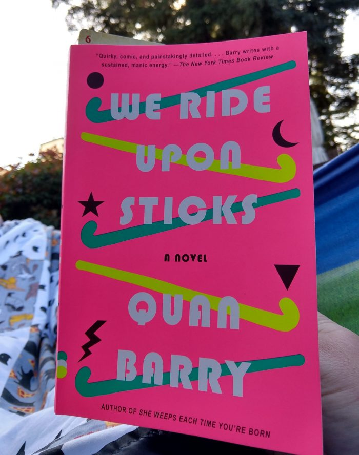 book cover of We Ride Upon Sticks, taken outside while I'm lying in the hammock. The cover is bright pink and has a late 80s style