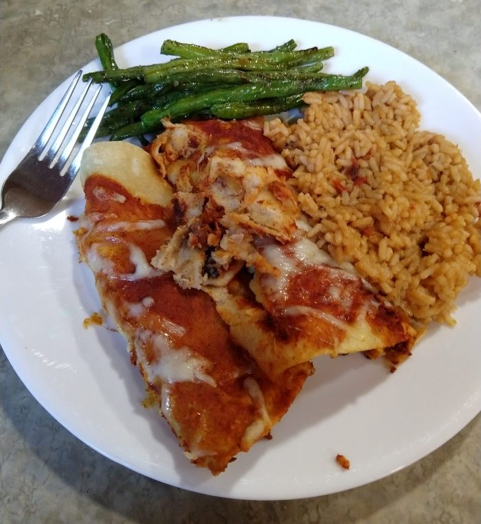 a plate with two enchaladas, roasted green beans and spanish rice