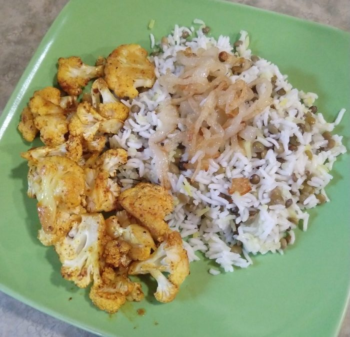a plate of a lentil and rice dish topped with onions and cauliflower roasted with paprika and chili powder