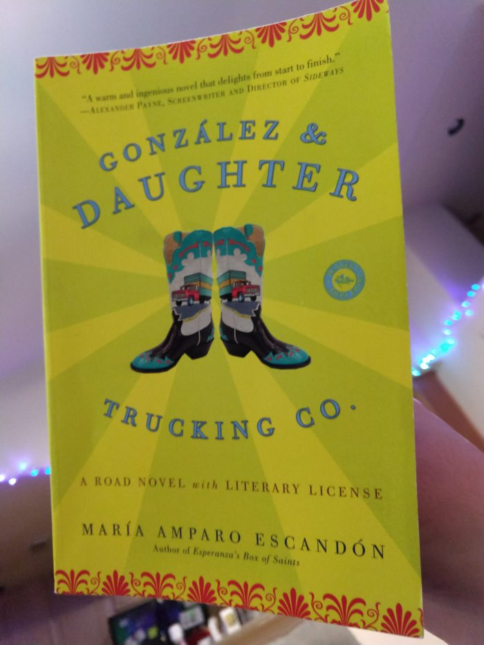 paperback book: González & Daughter Trucking Co. The cover is bright yellow and features cowboy boots with a truck on them