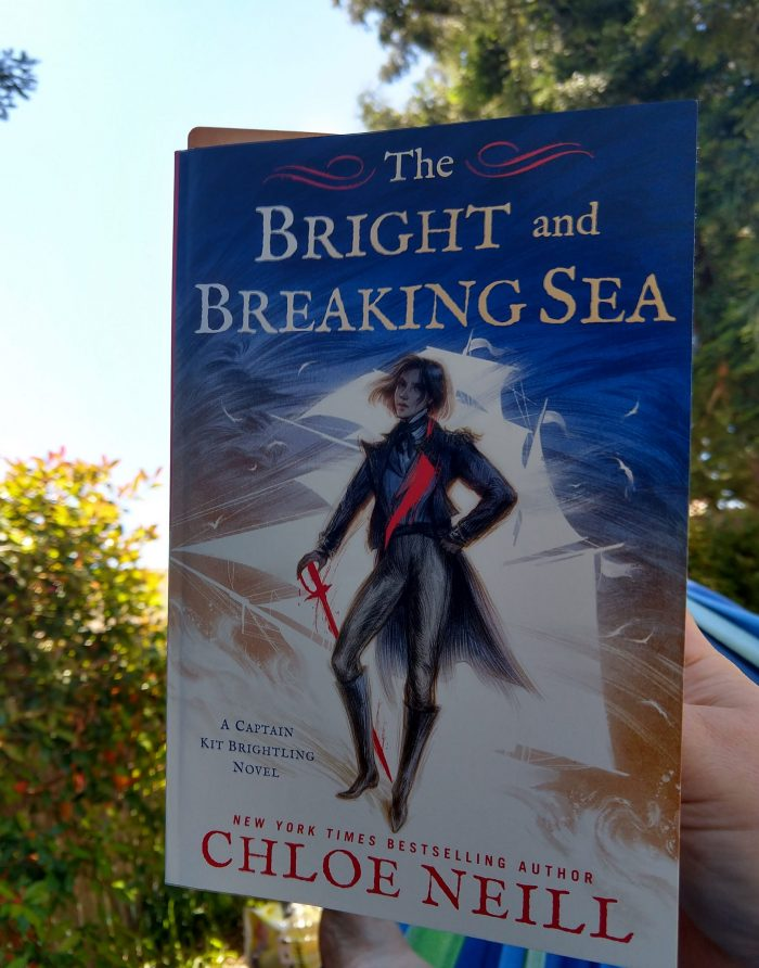 paperback book: The Bright and Breaking Sea. Photo taken outside. Trees in are in the background and it's a sunny day.