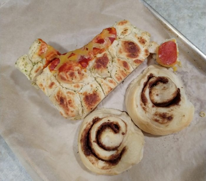 baked goods roughly resembling a skate: a chunk of garlic pull-apart bread is cut into the shape of a shape boot and has a small amount of pizza sauce to mark the tongue of the boot and cheese shreds for the laces. There are two cinnamon rolls below to represent the wheels