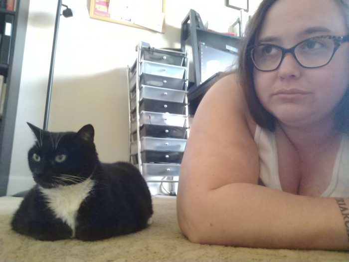 Huey the cat sitting on the floor, looking off camera. I am on the floor next to her looking in the same direction